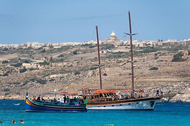 Veleros malteses atracados en el Blue Lagoon de Comino. Al fondo, Victoria, en Gozo. Foto de Alain Bachelier.